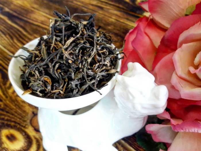 Чай дянь хун в миске рядом с розой